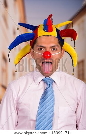 Silly happy handsome young businessman with a red clown nose and colorful harlequin hut in his head.