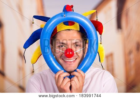Cheerful young businessman with a red clown nose and colorful harlequin hut in his head playing with a blue ballons around his head.