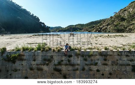 Man traveler sitting on a edge of the dam and taking selfie photo. Aerial photography. Photo was taken in The Tibi Dam (embalse de Tibi) is a masonry dam on Monegre River in Spain. It is one of the oldest dams in Europe