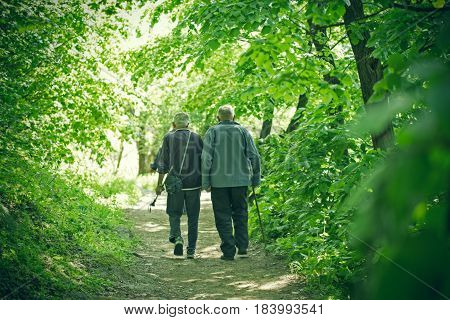 Two elderly persons (pensioners) walks in forest, healthy lifestyle, health concept
