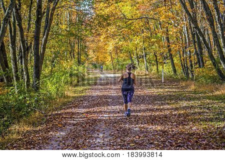 A young woman runs through this Autumn Park in Long Valley New Jersey.