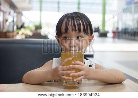 Asian little Chinese girl drinking lemon tea in outdoor cafe