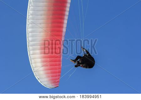 Paraglider flying in the blue sky as background