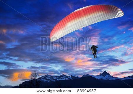 Paraglider flying over mountains in winter sunset