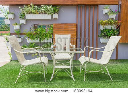 Set of white chair and table over the green grass garden