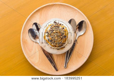Vanilla ice-cream scoops in white cup on wooden background