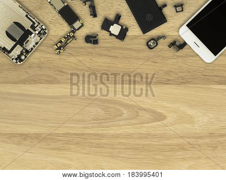 Flat Lay (Top view) of smart phone components on wooden background with copy space