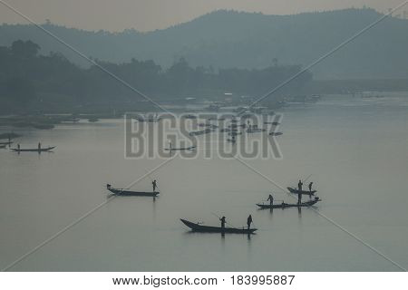 A fiery foggy sunrise sky looking out over the Son river in Phong Nha Vietnam. With fishing boats in silhouette.