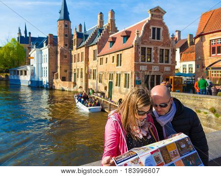 Bruges Belgium - 11 April 2017 - Tourist couple look at Bruges map on a stone bridge near a canal with background view of beautiful historic architecture of Bruges on April 11 2017.