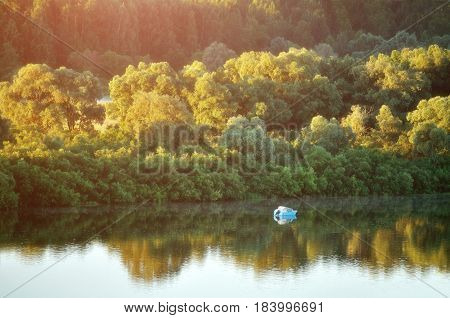 Summer water landscape with summer forest in the sunrise light. Birds eye view of of picturesque forest summer landscape with lonely boat on the summer river under soft morning summer sunlight. Summer forest background