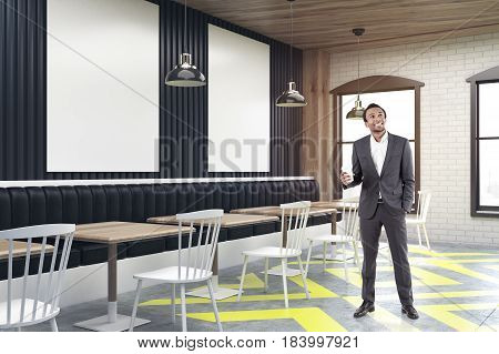 African American businessman standing in a corner of a cafe with posters hanging on a black wooden wall square tables and white chairs near them. 3d rendering mock up