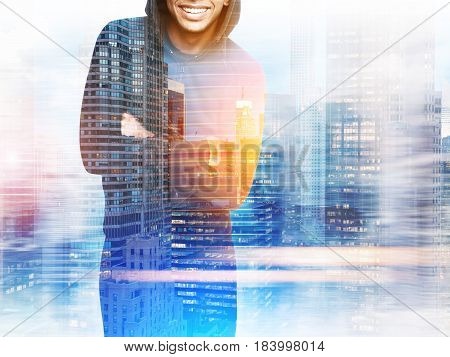 Close up of an unrecognizable African American sportsman standing in a hoodie against a night city panorama. Mock up toned image double exposure