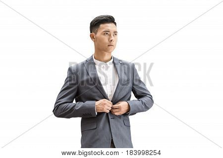 Isolated portrait of a young Asian businessman buttoning his dark gray suit and wearing a white shirt.