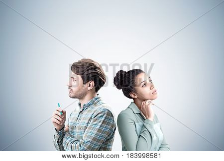 Portrait of an African American woman and her bearded colleague standing back to back near a blank gray wall. Mock up