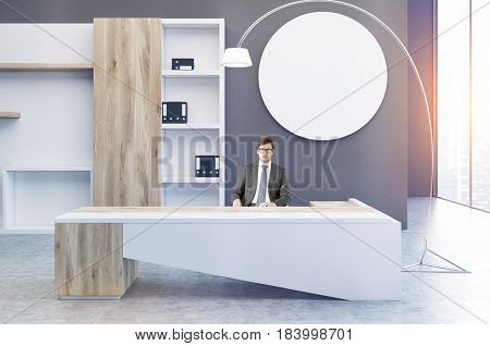 Interior of a clerk office with a gray wall a round poster hanging on it a large desk with a businessman at it and a bookcase with folders. 3d rendering mock up