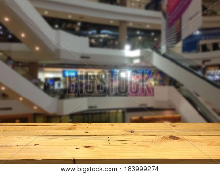 Empty wooden table space platform and blurred shopping mall background for product display montage.