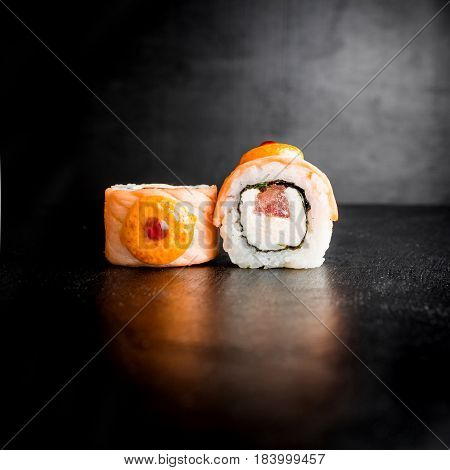 Sushi rolls with fish on dark background. Japanese traditional food.
