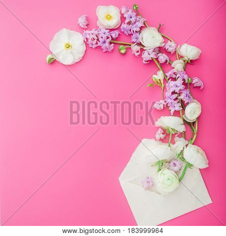 Floral pattern of white and pink flowers and envelope on pink background. Flat lay, top view. Flowers background.