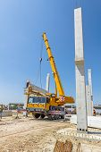 Mobile crane is operating and worker is assembly concrete joist in high place. Height worker is placing truss on building skeleton. poster