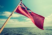 The uk red ensign the british maritime flag flown from yacht sail boat blue sky and baltic sea. Summer and travel voyage poster
