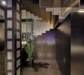 Restaurant in a loft style with brick and concrete walls, stairway with reticulated partition and glowing lamps. There is a column, big green cactus in the pot, door, signboard on the wall. poster
