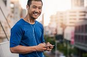 Portrait of a smiling young Asian man in sportswear standing outside listening to music on an mp3 player while out for a city run poster