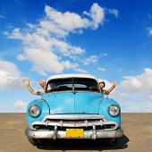 European senior couple having fun touring around Cuba, in an blue vintage oldtimer car poster