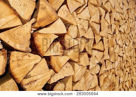 Background Image Of Stacked, Dry Chopped Logs Used For Firewood. Pile Of Logs Ready To Be Used In Fi