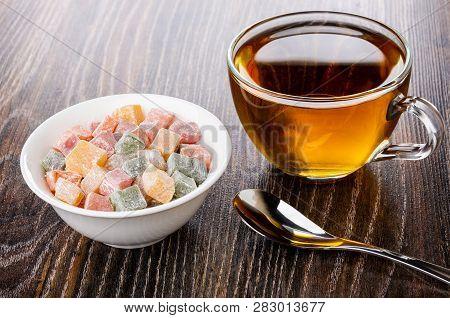 Multicolor Rakhat-lukum In White Bowl, Teaspoon, Transparent Cup With Tea On Dark Wooden Table