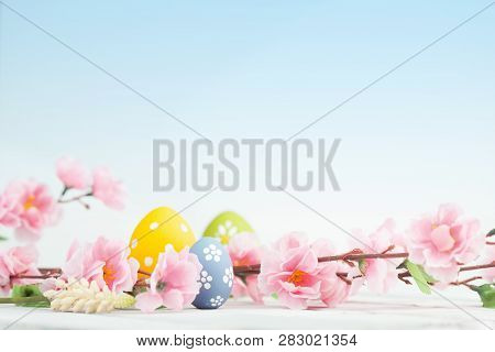 Easter Eggs And Pink Flowers Decoration On Blue Background