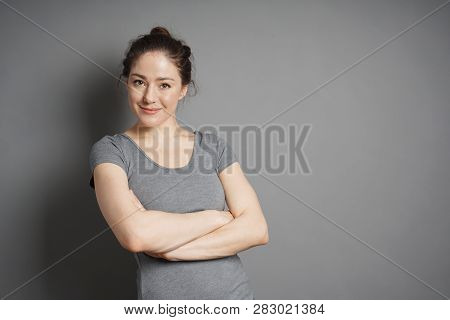 Young Woman With Contented Smile And Crossed Arms Against Gray Background With Copy Space