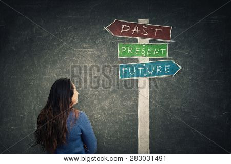 Rear View Woman In Front Of Blackboard Looking At A Signpost With Arrows Showing Past, Present And F