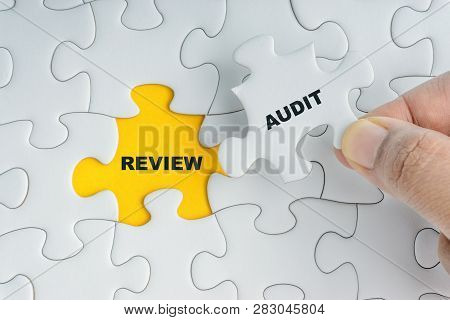Hand Holding Piece Of Jigsaw Puzzle With Word Audit Review. Selective Focus