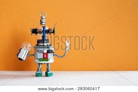 Funny Robotic Toy Holds Light Bulb. Creative Design Futuristic Humanoid Robot On Brown Gray Backgrou
