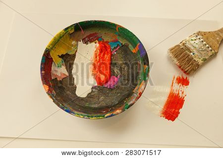 Painters Wooden Mixing Bowl With Wet White And Orange Paint Smeared Wet Paint On Paper And Paintbrus