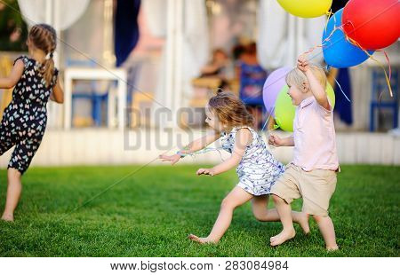 Little Boy And Girl Having Fun During Celebrating Birthday Party. Happy Child With With Colorful Bal