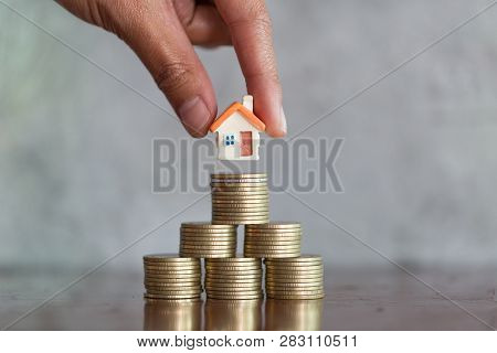 Men's Hand Is Planning Savings Money Of Coins To Buy A Home, Concept For Property Ladder, Mortgage A
