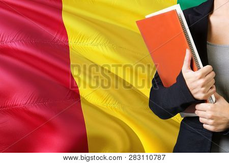Learning Guinean Language Concept. Young Woman Standing With The Guinea Flag In The Background. Teac