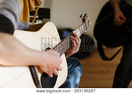 The Young Man Is A Soloist On An Acoustic Guitar, Playing With A Friend