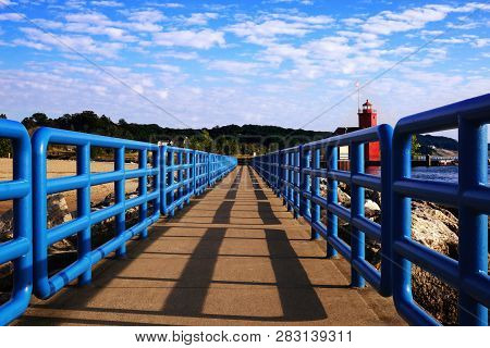 Pier With A Bright Blue Fence In Perspective. Big Red Lighthouse On The Lake Michigan. Holland Harbo