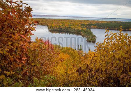 Michigan Autumn Scenic Panorama. Vibrant autumn color in the northern Michigan forest with the vast blue waters of Lake Superior in the background. Spectacle Lake overlook in Brimley, Michigan poster