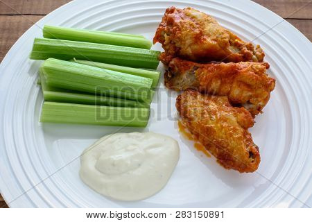 Buffalo chicken wings with celery and blue cheese on dish