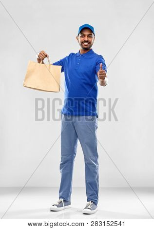 service and people concept - happy indian delivery man food in paper bag in blue uniform over grey background