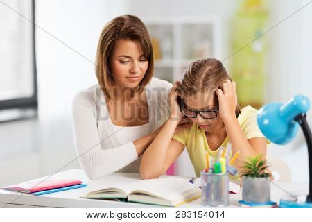 education, family and learning concept - mother helping daughter with difficult homework task at home