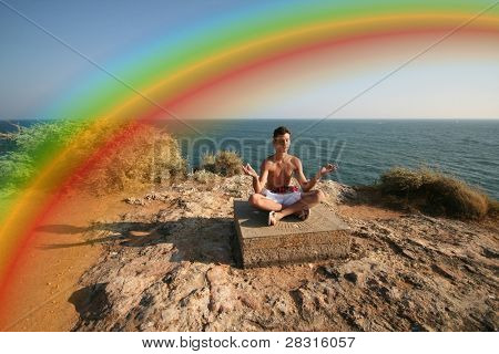 man doing yoga under a rainbow