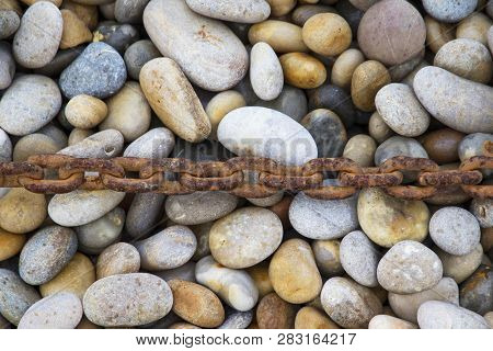 Rusty Chain Laid On Pebbles, Chesil Beach, Weymouth, Dorset