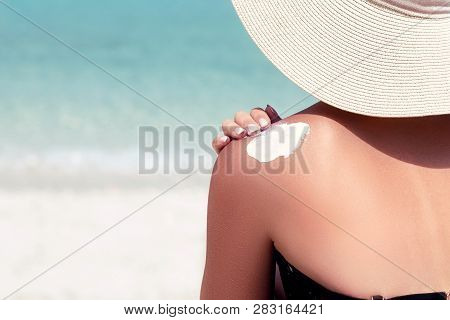 Woman Applying Sunscreen Creme On  Tanned  Shoulder. Skincare. Sun Protection Sun Cream. Bikini Hat