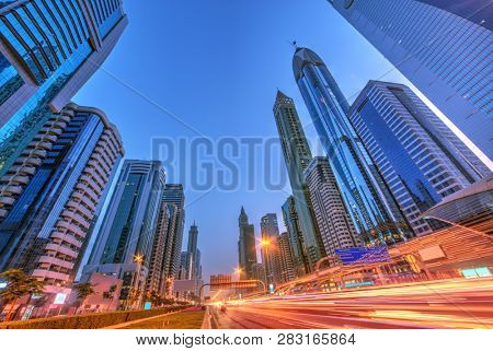 Modern street view with blur traffic, Dubai. Super modern city and transportation concept. Long exposure, blur lights of cars. Dubai is super modern city in UAE.