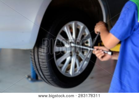 The Blure Of Mechanic In Blue Uniform Using Cross Wrench Tighten The Bolts Wheel