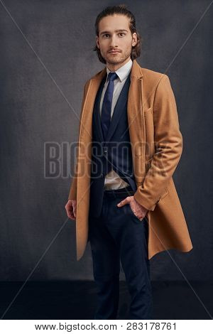 Portrait Of A Stylish Young Handsome Long-haired Unshaven Man In Light Brown Blazer And Blue Necktie